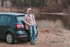 Młodego człowieka kierowca zatrzymujący i odpoczywa blisko samochodu podczas podróży przerwy zdjęcia stock