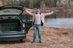 Młodego człowieka kierowca zatrzymujący i odpoczywa blisko samochodu podczas podróży przerwy fotografia royalty free