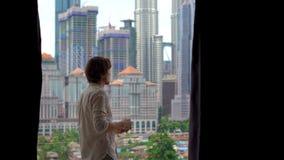 Młodego człowieka komes balkon jego mieszkanie z widokiem na centrum miasta pełno skyscrappers i napoje jego ranek zdjęcie wideo