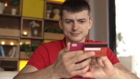 Młodego człowieka kupienia towary od interneta na jego smartphone z jego kredytową kartą zdjęcie wideo