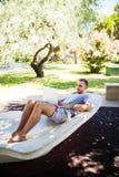 Młodego człowieka lying on the beach na ławce z laptopem uczeń studiuje na ulicie zdjęcia stock