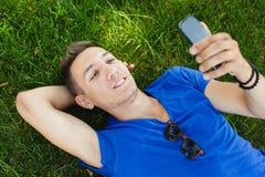 Młodego człowieka lying on the beach na trawie i używać mądrze telefon fotografia royalty free