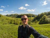Młodego człowieka makin selfie na zieleń krajobrazu tle Obrazy Stock