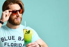 Młodego człowieka margarita koktajlu napoju soku szczęśliwy ono uśmiecha się wskazujący jeden palec przy kamerą Zdjęcia Royalty Free