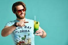 Młodego człowieka margarita koktajlu napoju soku szczęśliwy ono uśmiecha się wskazujący jeden palec przy kamerą Obraz Stock