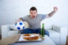 Młodego człowieka mienia dopatrywania balowy mecz futbolowy na tv leżance z pizzą i piwem świętuje w domu szalonego cel lub zwyci Zdjęcia Royalty Free