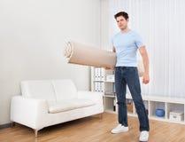 Młodego Człowieka mienia dywan fotografia stock
