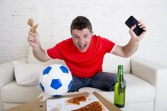 Młodego człowieka mienia pieniądze w jego i telefon komórkowy wręczamy dopatrywania fottball grę na telewizyjnym internecie upraw obraz royalty free