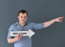Młodego człowieka mienia powitania deski sztandar i wskazywać coś, stojący na ciemnym tle Fotografia Stock