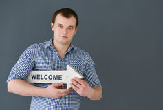 Młodego człowieka mienia powitania deski sztandar, stoi na ciemnym tle Zdjęcia Royalty Free