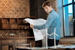 Młodego człowieka mienia projekt i patrzeć silniki wiatrowych Obraz Stock