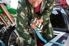 Młodego człowieka mienia puszka patka próbuje zabezpieczać brudu roweru moto fotografia stock