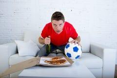 Młodego człowieka mienia samotnej piłki i piwnej butelki dopatrywania mecz futbolowy na telewizi kanapy leżance w domu Obraz Royalty Free