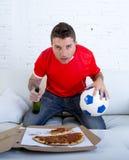 Młodego człowieka mienia samotnej piłki i piwnej butelki dopatrywania mecz futbolowy na telewizi kanapy leżance w domu Obrazy Royalty Free