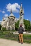 Młodego człowieka modniś w szkłach zbliża katedrę Notre Damae De P Zdjęcia Royalty Free