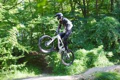 Młodego człowieka moutain ćwiczy rower w lesie zdjęcia stock