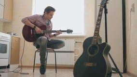 Młodego człowieka muzyk komponuje muzykę na gitarze i sztuki w kuchni, inny instrument muzyczny w przedpolu, zdjęcia royalty free