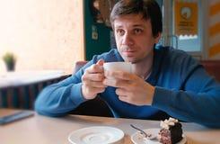 Młodego człowieka napój herbata w kawiarni zdjęcia royalty free