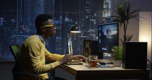 Młodego człowieka obsiadania edytorstwo i plecy wideo wśrodku pokoju obrazy stock