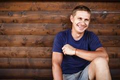 Młodego człowieka obsiadanie i relaksować na drewnianym pokładzie plenerowym Obraz Stock