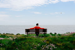 Młodego człowieka obsiadanie na ławce, patrzeje morze Zdjęcia Stock