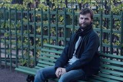 Młodego człowieka obsiadanie na ławce w lato ogródzie petersburg Rosji st Sławni miejsca Zdjęcia Royalty Free