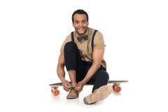 Młodego człowieka obsiadanie na deskorolka i wiązać shoelaces fotografia royalty free