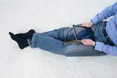 Młodego człowieka obsiadanie na dywanie z pastylką Obraz Stock