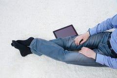 Młodego człowieka obsiadanie na dywanie z pastylką Fotografia Stock