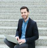 Młodego człowieka obsiadanie na krokach i ono uśmiecha się z laptopem Obraz Stock