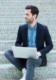 Młodego człowieka obsiadanie na krokach z laptopem Obraz Stock