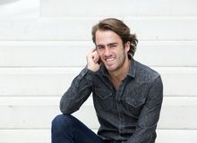 Młodego człowieka obsiadanie na krokach z telefonem komórkowym Zdjęcie Royalty Free