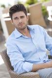 Młodego człowieka obsiadanie na krześle przy outdoors kawiarnią Zdjęcia Stock