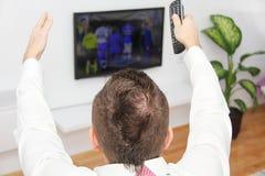 Młodego człowieka obsiadanie na leżance ogląda mecz futbolowego na tv Fotografia Royalty Free
