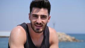 Młodego człowieka obsiadanie na plażowy samotnym osamotniony i zbiory