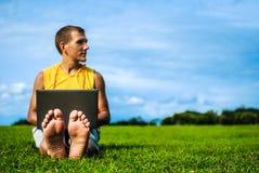 Młodego człowieka obsiadanie na trawie i działanie z laptopem Zdjęcie Royalty Free
