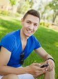 Młodego człowieka obsiadanie na trawie i używać mądrze telefon Obrazy Stock