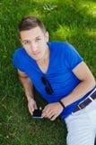 Młodego człowieka obsiadanie na trawie i używać mądrze telefon obraz stock