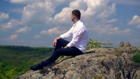 Młodego człowieka obsiadanie przegapia lesistą dolinę zdjęcie wideo