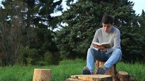 Młodego człowieka obsiadanie w czytaniu i parku książka zbiory wideo