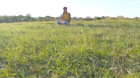 Młodego człowieka obsiadanie w joga pozie przy zieloną trawą w łące i medytuje Mięśniowy facet relaksuje w lotos pozie przy natur Zdjęcia Royalty Free