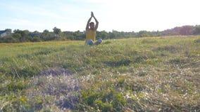 Młodego człowieka obsiadanie w joga pozie przy zieloną trawą w łące i medytuje Mięśniowy facet relaksuje w lotos pozie przy natur Zdjęcie Stock