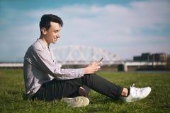 Młodego człowieka obsiadanie w parku i texting wiadomość Młody człowiek w parkowym obsiadaniu na trawie z smartphone zdjęcia stock