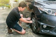 Młodego człowieka odmieniania koło jego samochód na drodze zdjęcie royalty free