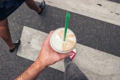 Młodego człowieka odprowadzenie na zebry skrzyżowaniu w mieście z kawą g zdjęcie royalty free