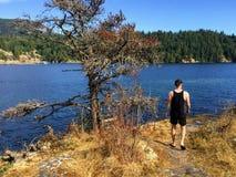 Młodego człowieka odprowadzenie wzdłuż ścieżki mała Aleksander wyspa przegapia ocean zachód zatoka i stały ląd gambir wyspa obraz royalty free