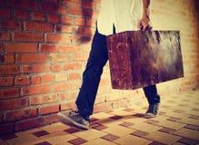 Młodego człowieka odprowadzenie wzdłuż ulicy z starą walizką, Zdjęcie Royalty Free