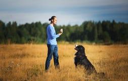 Młodego człowieka odprowadzenie z Bernese góry psem na lata polu obrazy stock