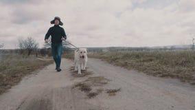 Młodego człowieka odprowadzenie z jego psem wzdłuż drogi gruntowej zbiory wideo