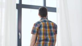 Młodego człowieka otwarcia nadokienna zasłona w domu zbiory wideo